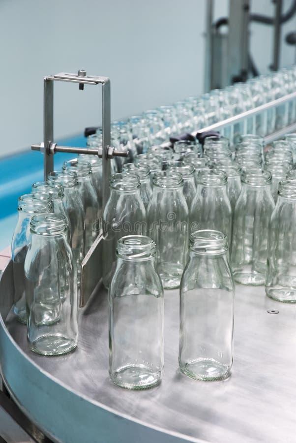 Стеклянные бутылки на конвейерной ленте стоковая фотография