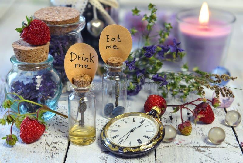 Стеклянные бутылки с бирками едят меня, выпивают меня, винтажную ягоду часов, свечи и лета на таблице стоковое фото rf