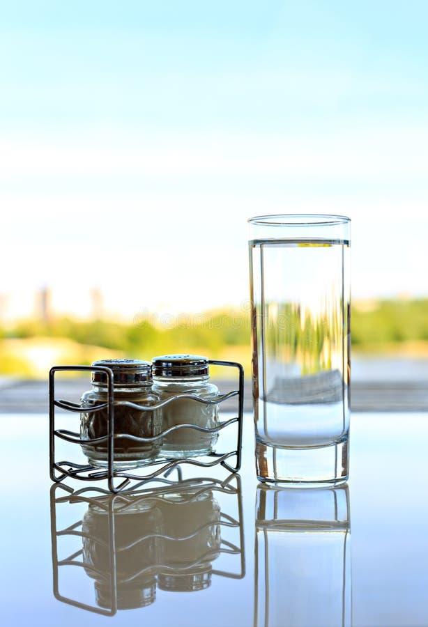 Стеклянные шейкеры соли и перца с стеклом воды на белой таблице с предпосылкой отражения и лета стоковое фото rf