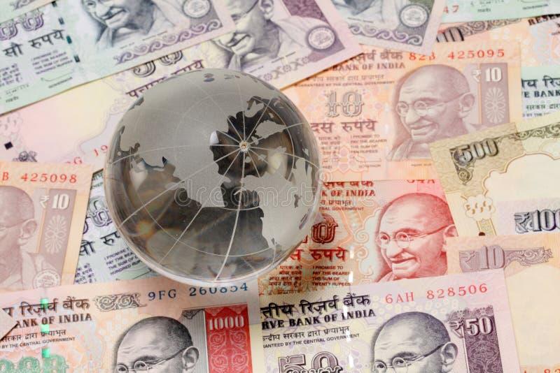 Стеклянный глобус на индийской валюте стоковое фото