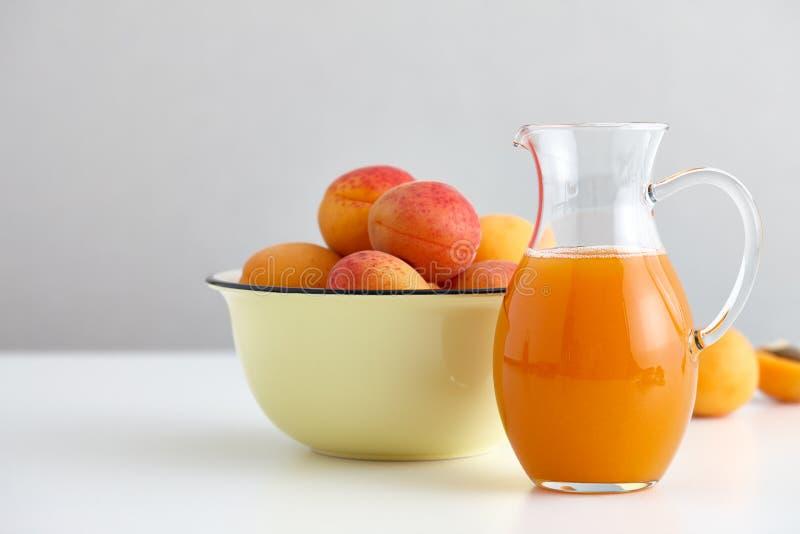 Стеклянный кувшин с свежим соком и зрелым шаром абрикосов стоковое фото