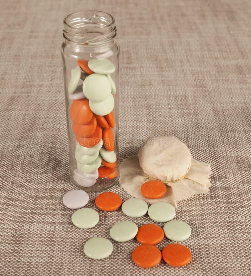 Стеклянный опарник с малыми покрашенными конфетами на предпосылке холста стоковое изображение