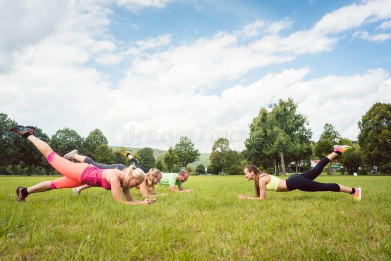 Стелюга семьи outdoors в луге с учителем фитнеса стоковое фото