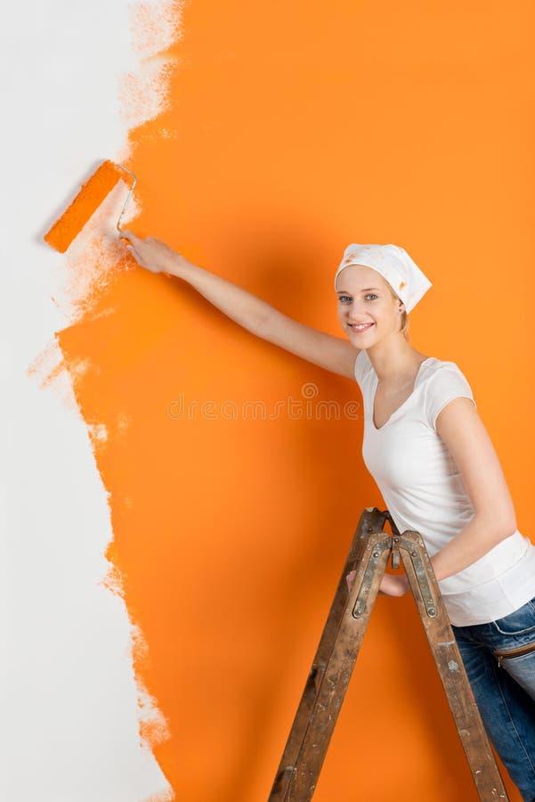 Стена картины молодой женщины с роликом в доме стоковое фото rf