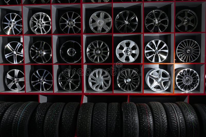 Стена колес автомобиля сплава и пневматических автошин в магазине сезонное хранение колеса стоковые фотографии rf
