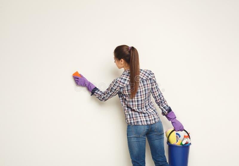 Стена молодой женщины моя с губкой стоковые фотографии rf