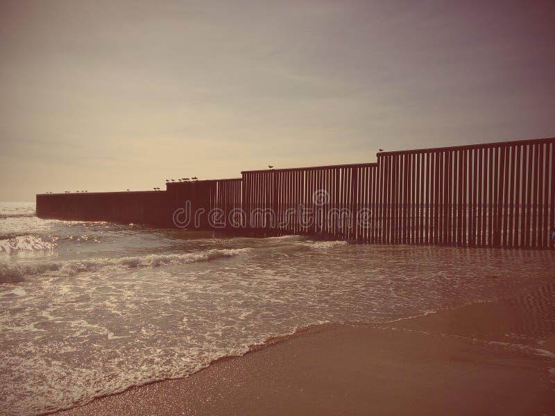 Стена на пляже USA-MEXICO стоковые изображения rf