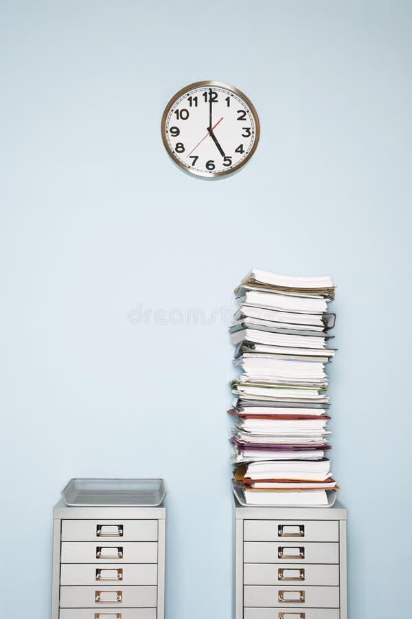 Стена офиса с стогом часов обработки документов внутри outbox на картотеке стоковое изображение rf