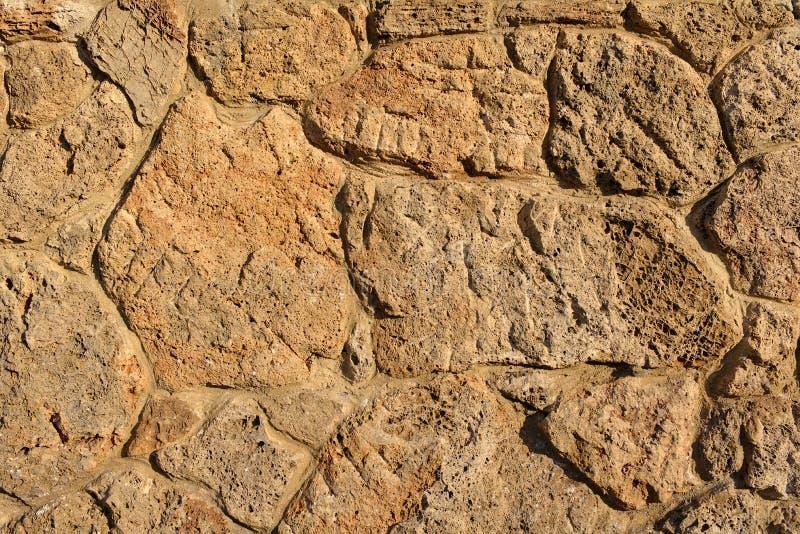 Стена песчаника сделанная скачками пористых частей камня осветила солнцем вечера стоковые изображения rf