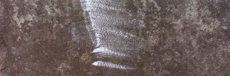 Стена покрытая со старым кроша гипсовым цементом с трассировками белой краски стоковая фотография