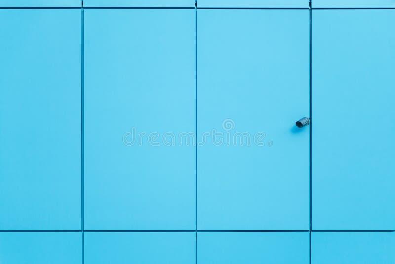 Стена покрыта с голубыми панелями и камерой слежения отделки абстрактное архитектурноакустическое небо детали здания предпосылки стоковое фото