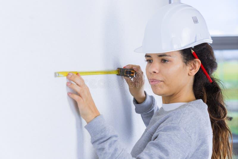 Стена построителя женщины измеряя стоковые фото