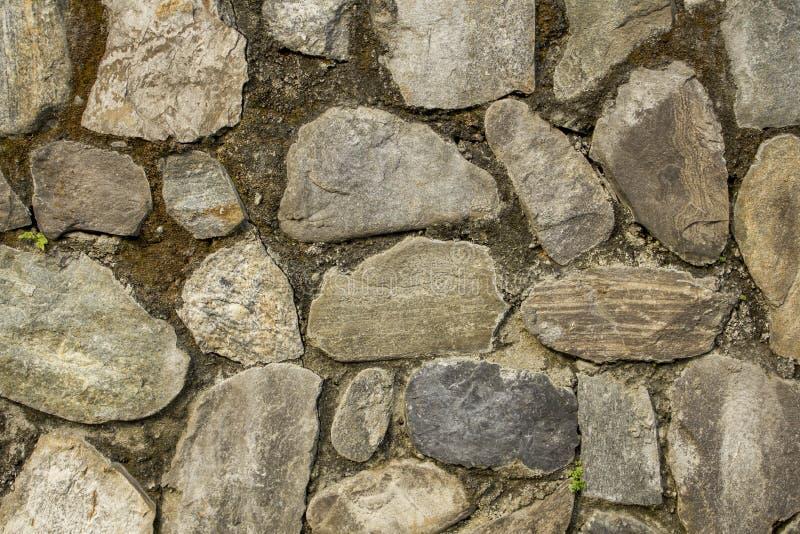 Стена различных больших естественных камней Стена с мхом грубая текстура поверхности стены серые, голубые и белые камни стоковое изображение rf