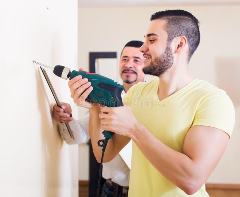Стена сына и отца сверля стоковое изображение rf