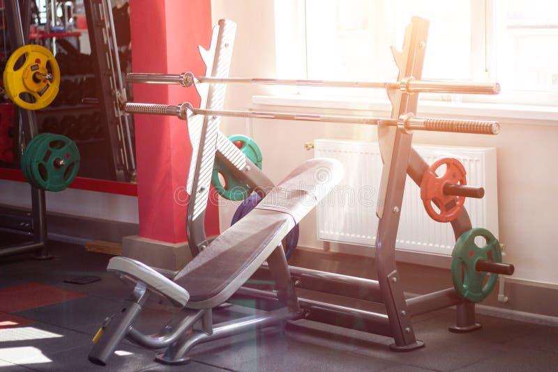 Стенд спорт со штангой и диски на шкафе для того чтобы выполнить жим лежа штанги в современном спортзале, мускулатуре, солнце стоковая фотография