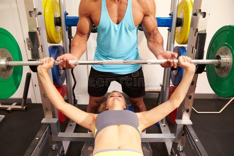 Стенд женщины отжимая весы с помощью тренера, вид спереди стоковые фотографии rf