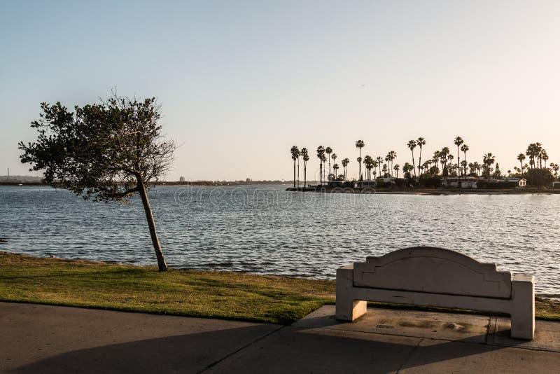 Стенд и дерево на заходе солнца на парке залива полета стоковые фото