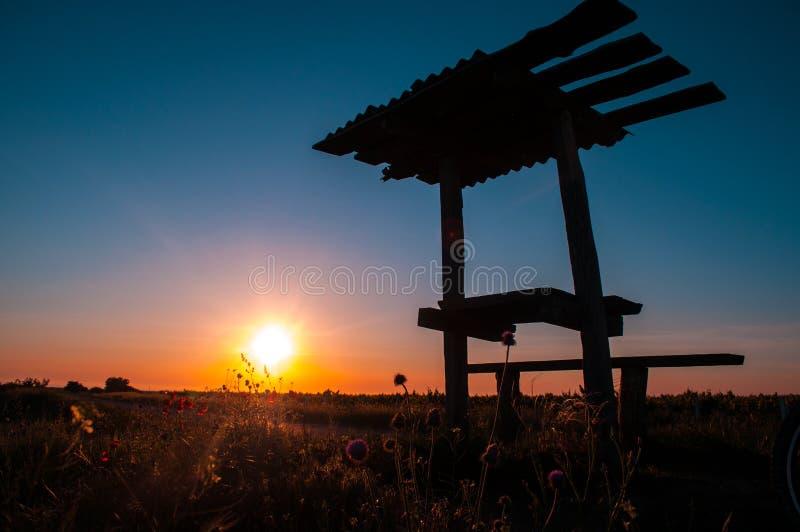 Стенд и дерево пикника Silhouetted на заходе солнца стоковое изображение rf