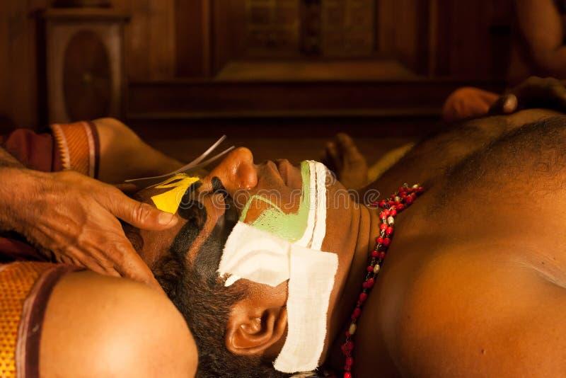 Степень Kathakali подготавливая для представления путем прикладывать состав стороны стоковая фотография