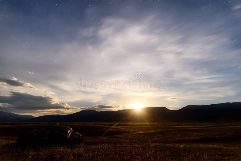 Степь гор играет главные роли небо облаков луны стоковое фото rf