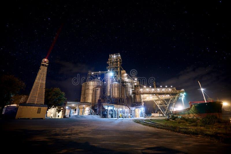 Стержень зерна на морском порте с звёздным небом на предпосылке Хлопья ссыпают перегрузка от безрельсового транспорта к сосуду на стоковые изображения