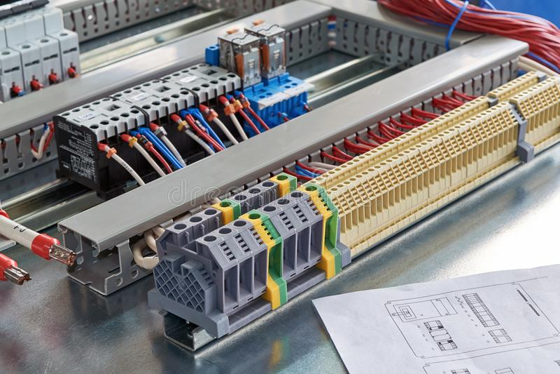 Стержни, контакторы, реле, автоматы защити цепи и электрический чертеж шкафа стоковая фотография