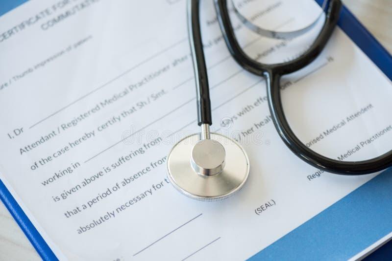 Стетоскоп лежа на доске сзажимом для бумаги с диагнозом в медицинской клинике стоковое фото