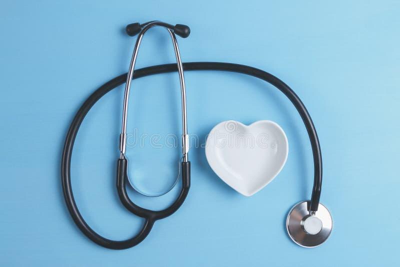Стетоскоп и белый в форме сердц поддонник на голубой деревянной предпосылке стоковые фото