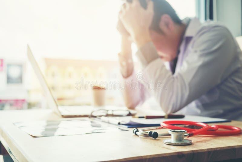 Стетоскоп и доктор сидя с компьтер-книжкой усиливают головную боль около стоковое фото