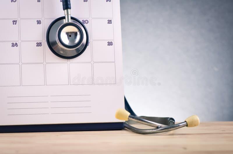 стетоскоп и календарь на деревянном столе над нежно освещенной темной стоковое фото rf