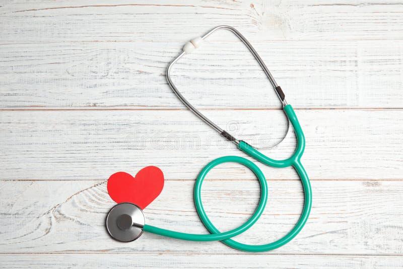 Стетоскоп и красное сердце на деревянной предпосылке, взгляде сверху стоковое изображение