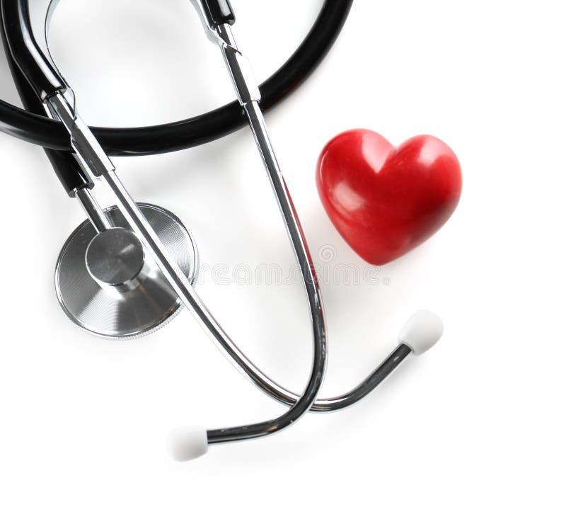 Стетоскоп и малое красное сердце на светлой предпосылке стоковое изображение rf