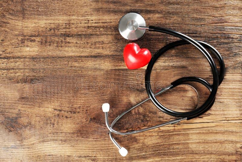 Стетоскоп и малое красное сердце на светлой предпосылке стоковые изображения rf