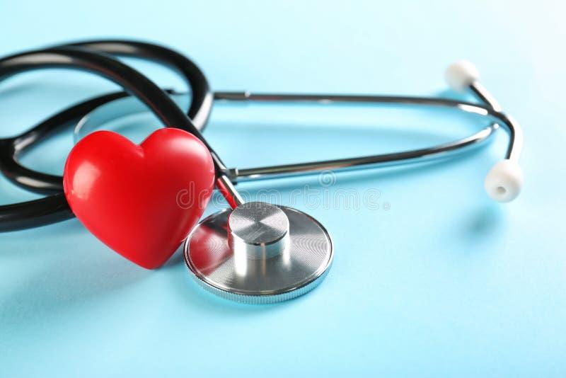 Стетоскоп и малое красное сердце на таблице стоковые фотографии rf