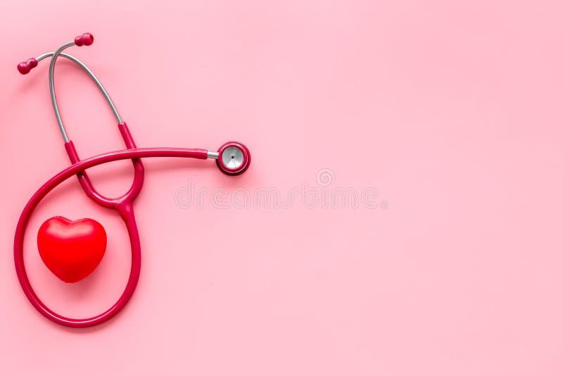 Стетоскоп и сердце для набора семейного врача, который нужно вылечить сердечного заболевания на розовом космосе взгляда сверху пр стоковая фотография