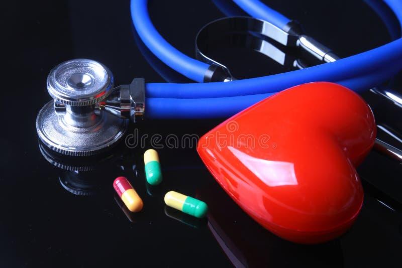Стетоскоп, красное сердце и сортированные pils на черной предпосылке зеркала Селективный фокус стоковые фотографии rf