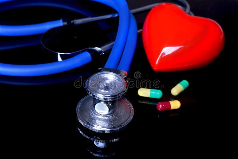 Стетоскоп, красное сердце и сортированные pils на черной предпосылке зеркала Селективный фокус стоковые фото