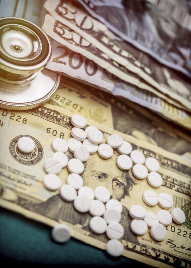 Стетоскоп на американских билетах вместе со шлюпкой белых таблеток стоковые изображения rf