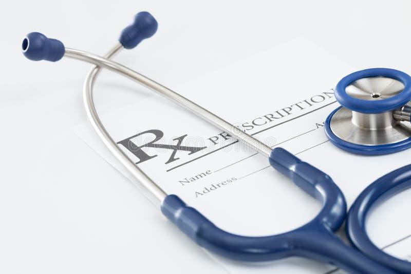 Стетоскоп с медицинским рецептом лекарства на таблице стоковое изображение