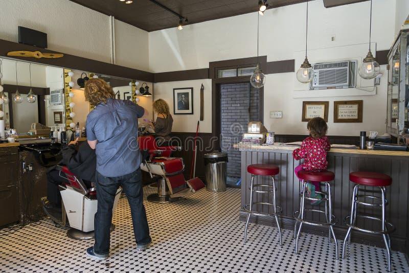 Стилизаторы на работе и малая девушка на табуретке в винтажном салоне парикмахерских услуг стиля стоковые фото