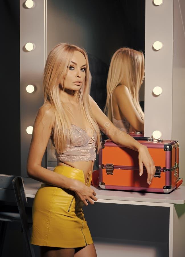 Стилизатор женщины с случаем состава в салоне красоты Визажист или фотомодель в уборной Чувственная женщина в сексуальном стоковая фотография