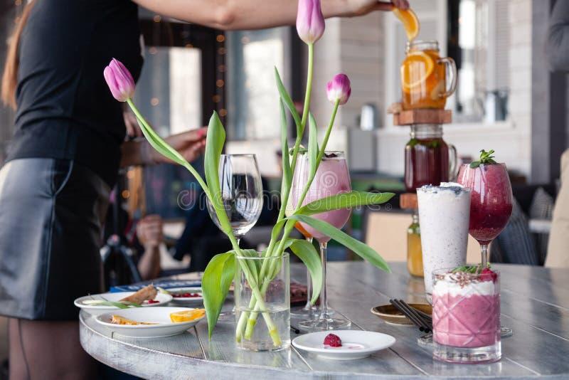 Стилизатор и фотограф еды украшают, подготавливающ снять различные коктейли, milkshakes, smoothies, вазу тюльпанов цветка на табл стоковые изображения