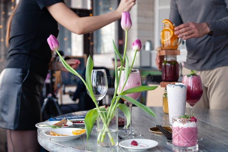Стилизатор и фотограф еды украшают, подготавливающ снять различные коктейли, milkshakes, smoothies, вазу тюльпанов цветка на табл стоковые изображения rf
