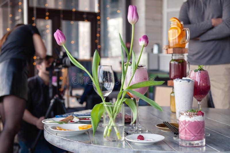 Стилизатор и фотограф еды украшают, подготавливающ снять различные коктейли, milkshakes, smoothies, вазу тюльпанов цветка на табл стоковые фотографии rf