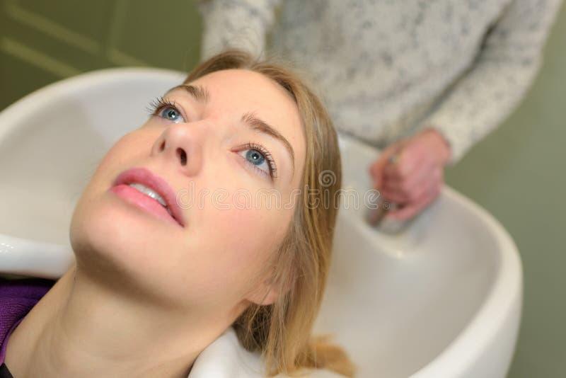Стилизатор моя и расчесывая волосы женщины в бассейне hairsalon стоковые изображения rf