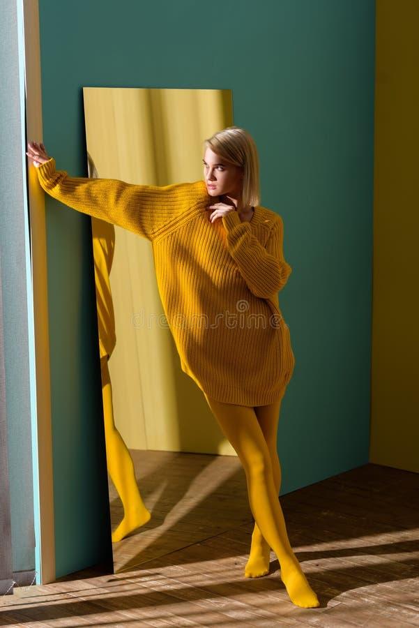 стильная белокурая женщина в желтом положении свитера и колготков стоковая фотография rf