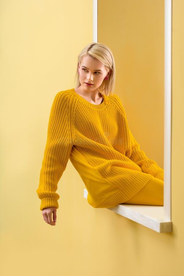 стильная белокурая женщина в желтом усаживании свитера стоковые изображения rf