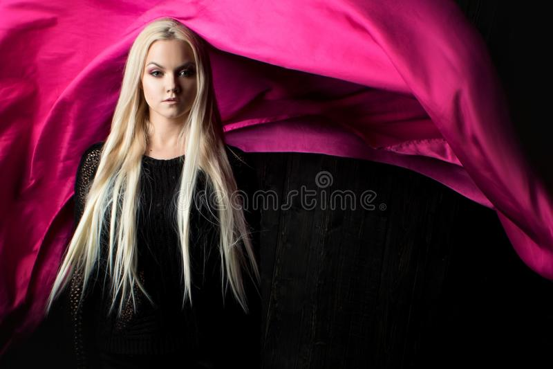 Стильная блондинка на темной предпосылке с яркой тканью летания, красит пинк стоковые фотографии rf