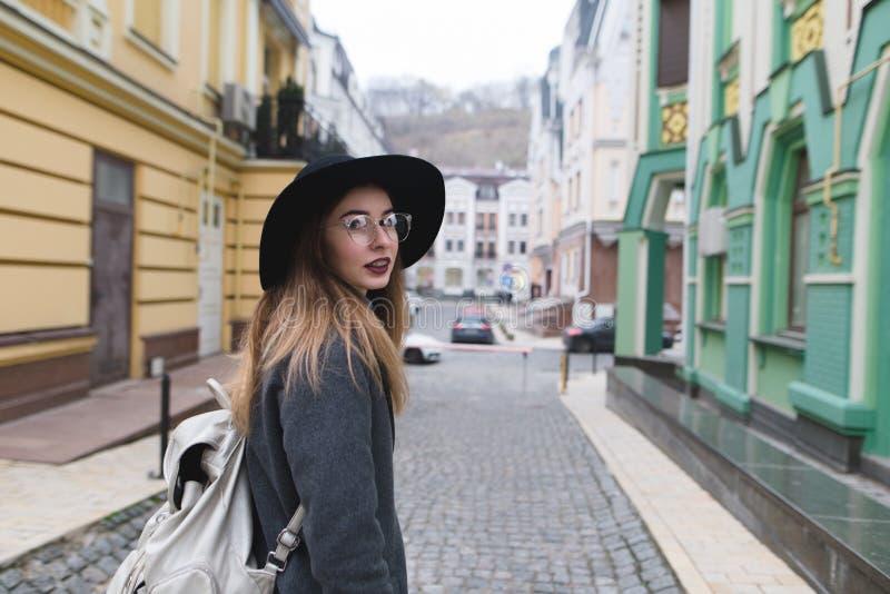 Стильная девушка в пальто и шляпе идет вокруг старого городка и смотрит камеру Перемещения красивые женщины стоковые фотографии rf