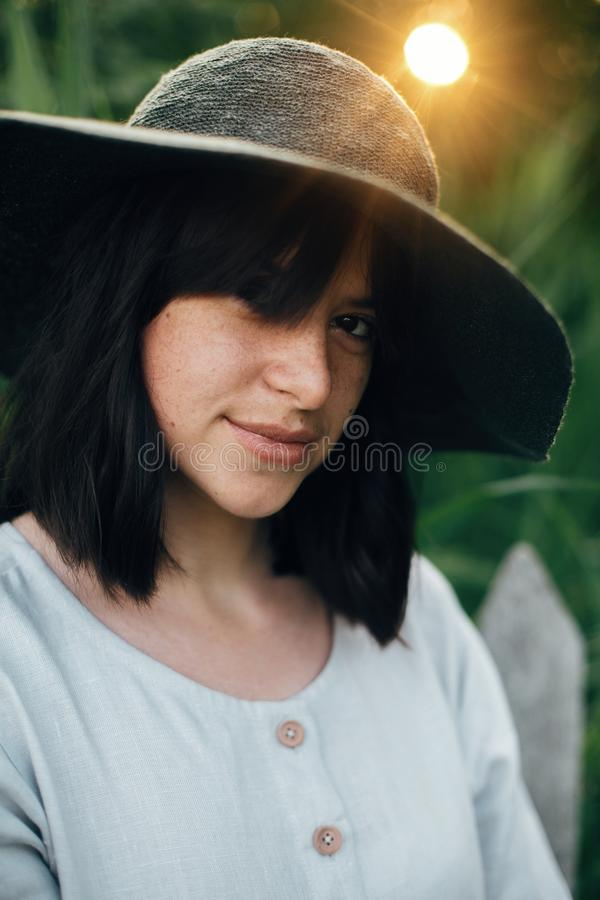 Стильная девушка в платье белья представляя на деревянных загородке и траве в заходе солнца Портрет женщины boho в шляпе в сельск стоковое фото rf